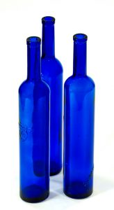 Three blue glass tequila bottles against white background